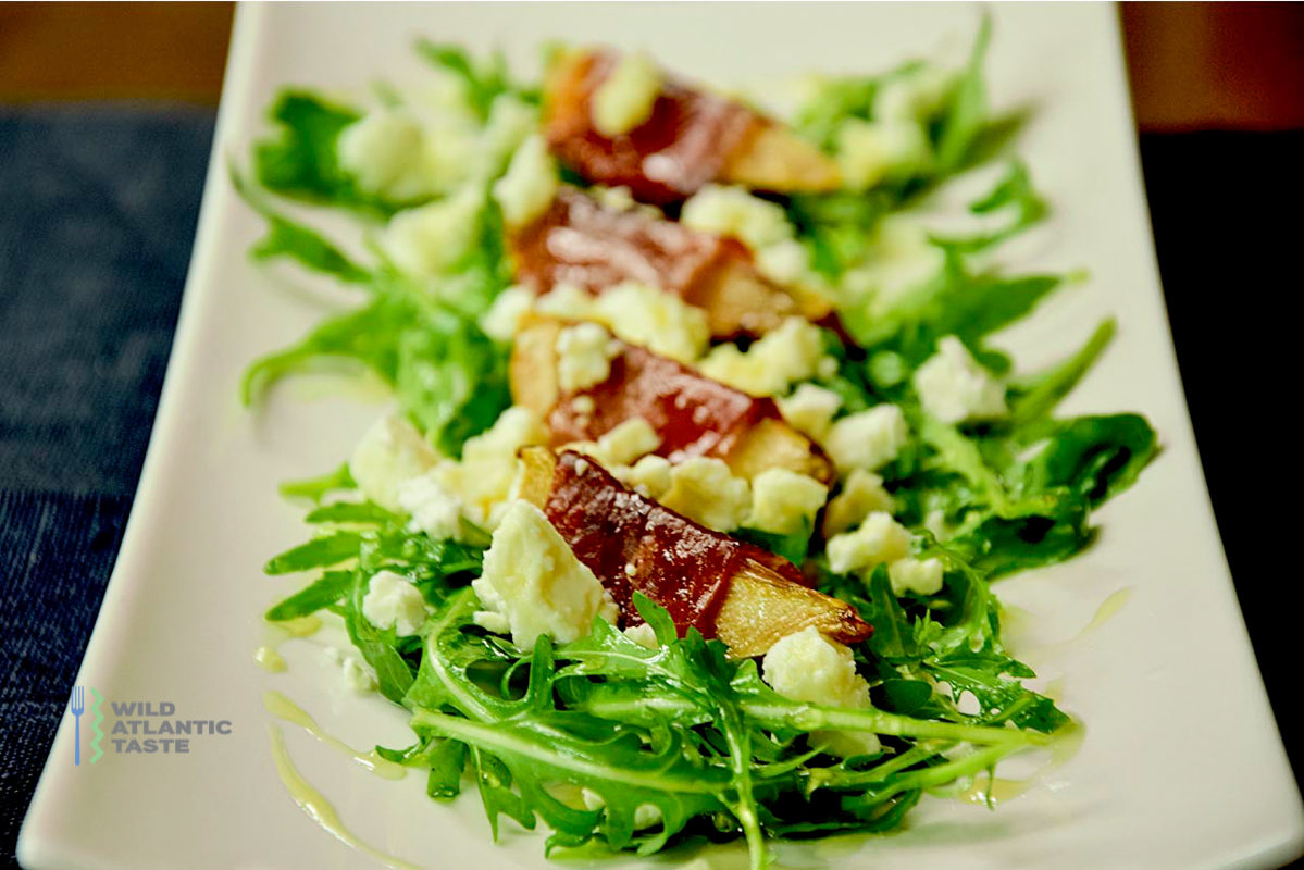 Baked pear wrapped in parma ham with rocket salad and feta cheese